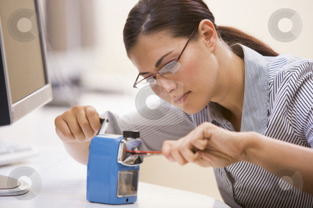 Woman in computer room using pencil sharpener stock photo,  by Monkey Business Images