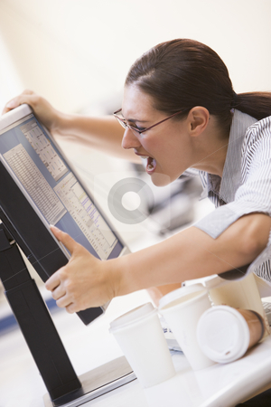 Woman in computer room grabbing her monitor and screaming stock photo,  by Monkey Business Images