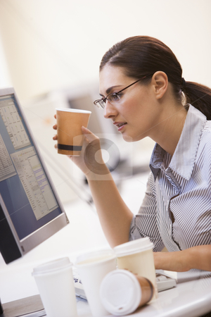 Woman in computer room with many cups of empty coffee around her stock photo,  by Monkey Business Images