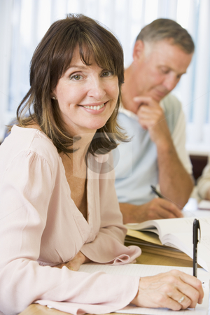 Middle aged woman studying with other adult students stock photo,  by Monkey Business Images