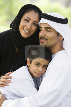 A Middle Eastern couple and their son sitting in a park stock photo,  by Monkey Business Images