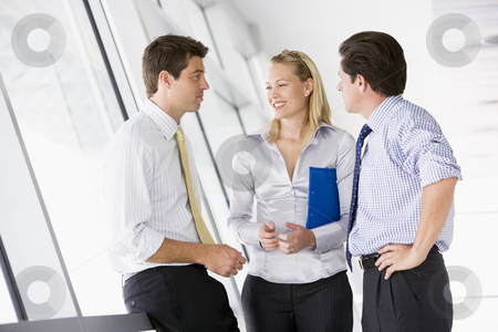 Three businesspeople standing in corridor talking and smiling stock photo,  by Monkey Business Images