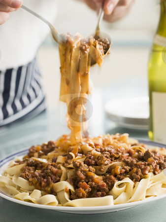 Tagaliatelle with Ragu Sauce stock photo, Man serving Tagaliatelle with Ragu Sauce by Monkey Business Images