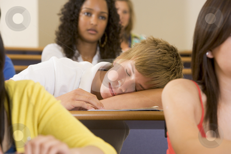Male college student sleeping through a university lecture stock photo,  by Monkey Business Images