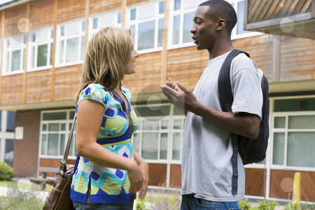 Male and female college students talking on campus stock photo,  by Monkey Business Images