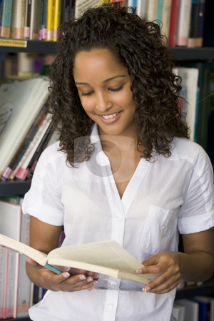 Female college student reading in a library stock photo,  by Monkey Business Images