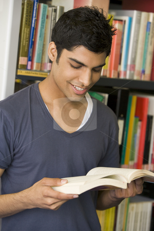 Male college student reading in a library stock photo,  by Monkey Business Images