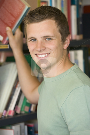 Male college student reaching for a library book stock photo,  by Monkey Business Images