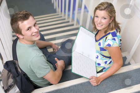 Male and female college students sitting on stairs stock photo,  by Monkey Business Images