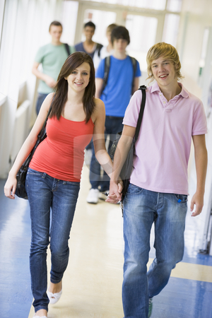 Young couple walking down university corridor stock photo,  by Monkey Business Images