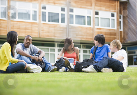 College students sitting and talking on campus lawn stock photo,  by Monkey Business Images