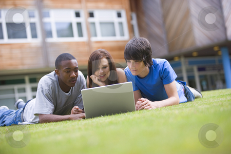 College students using laptop on campus lawn stock photo,  by Monkey Business Images
