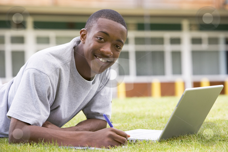 College student using laptop on campus lawn stock photo,  by Monkey Business Images