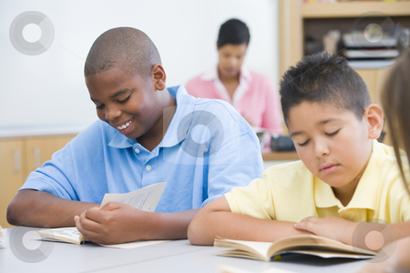 Elementary school classroom stock photo, Group of students reading books at desk by Monkey Business Images