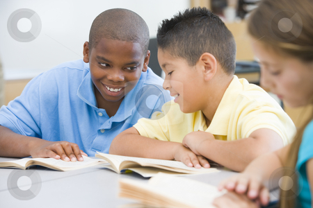 Elementary school classroom stock photo, Two boys discussing book whilst seated at desk by Monkey Business Images