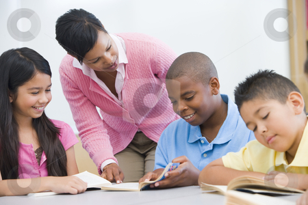 Elementary school classroom stock photo, Teacher helping elementary school reading group by Monkey Business Images