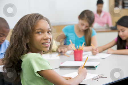 Elementary school pupil in classroom stock photo, Elementary school pupil working at desk by Monkey Business Images