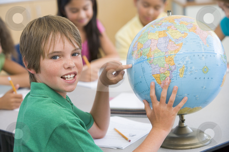 Elementary school pupil with globe stock photo, Elementary school pupil in geography lesson by Monkey Business Images