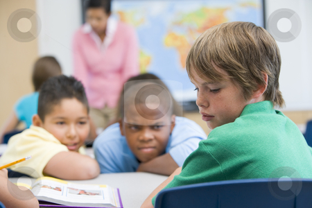 Boy being bullied in elementary school stock photo, Boy being bullied in elementary school classroom by Monkey Business Images