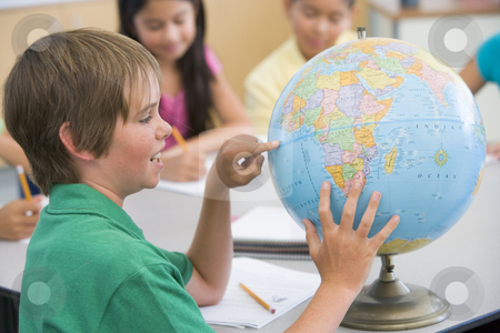 Elementary school geography class stock photo, Elementary school geography class with globe by Monkey Business Images