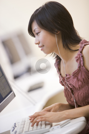 Woman in computer room listening to MP3 player while typing and  stock photo,  by Monkey Business Images