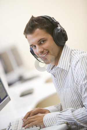 Man wearing headphones in computer room typing and smiling stock photo,  by Monkey Business Images