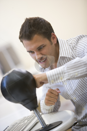 Man sitting in computer room using small punching bag for stress stock photo,  by Monkey Business Images