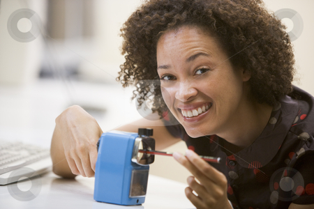 Woman in computer room using pencil sharpener and smiling stock photo,  by Monkey Business Images
