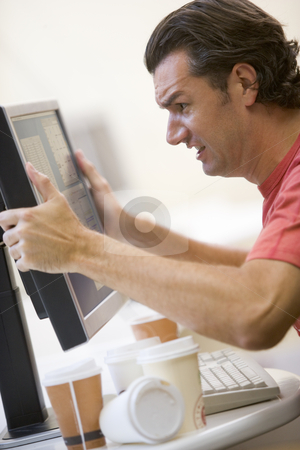 Man in computer room with many empty cups of coffee grabbing his stock photo,  by Monkey Business Images