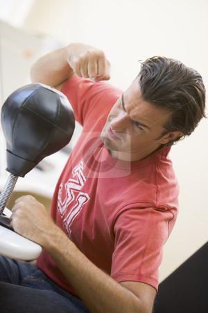 Man indoors using small punching bag stock photo,  by Monkey Business Images