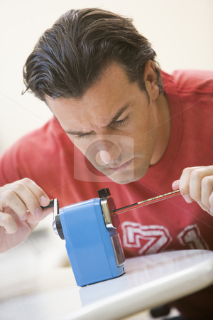 Man indoors using pencil sharpener stock photo,  by Monkey Business Images