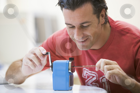 Man indoors using pencil sharpener smiling stock photo,  by Monkey Business Images