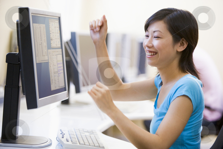Woman in computer room cheering and smiling stock photo,  by Monkey Business Images