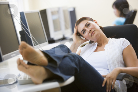 Woman in computer room with feet up thinking stock photo,  by Monkey Business Images