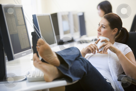Woman in computer room with feet up drinking coffee stock photo,  by Monkey Business Images