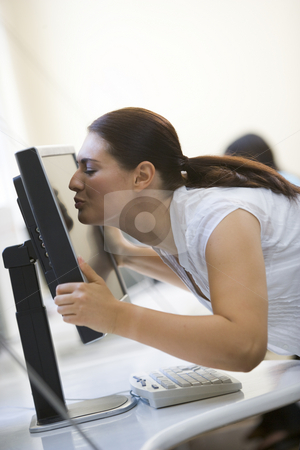 Woman in computer room kissing monitor stock photo,  by Monkey Business Images