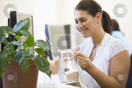 Woman in computer room watering plant smiling stock photo,  by Monkey Business Images