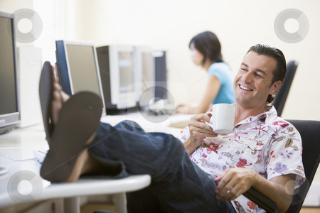 Man in computer room with feet up drinking coffee and smiling stock photo,  by Monkey Business Images