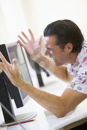 Man in computer room frustrated at monitor stock photo,  by Monkey Business Images