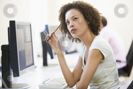Woman in computer room thinking stock photo,  by Monkey Business Images