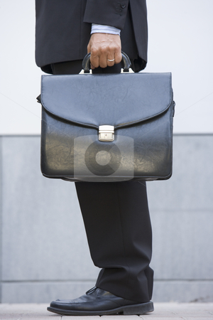 Businessman holding briefcase outdoors stock photo,  by Monkey Business Images