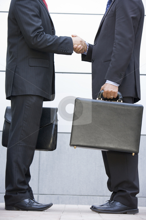 Two businessmen holding briefcases outdoors shaking hands stock photo,  by Monkey Business Images