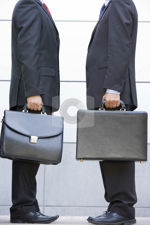 Two businessmen holding briefcases outdoors stock photo,  by Monkey Business Images