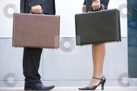 Two businesspeople holding briefcases outdoors stock photo,  by Monkey Business Images