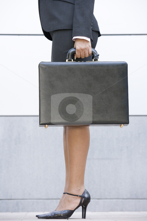 Businesswoman holding briefcase outdoors stock photo,  by Monkey Business Images