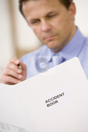 Businessman indoors looking at Accident Book stock photo,  by Monkey Business Images