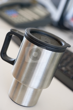 Shot of a reusable coffee cup on a desk stock photo,  by Monkey Business Images