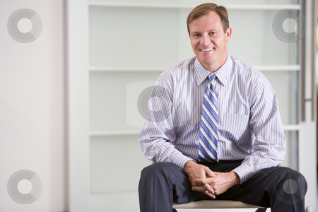 Businessman sitting indoors smiling stock photo,  by Monkey Business Images