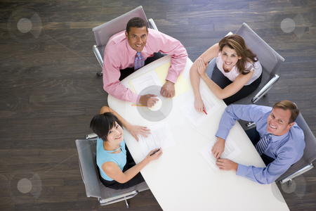 Four businesspeople at boardroom table smiling stock photo,  by Monkey Business Images