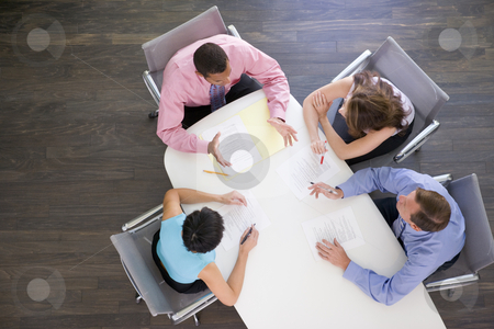 Four businesspeople at boardroom table stock photo,  by Monkey Business Images